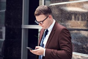 Man looking at his phone asking himself what to do after being served divorce papers