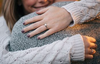Woman embracing her fiancé, showing off her engagement ring