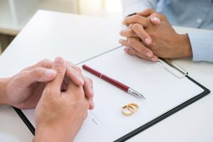 A divorcing couple signing documents in a contested divorce
